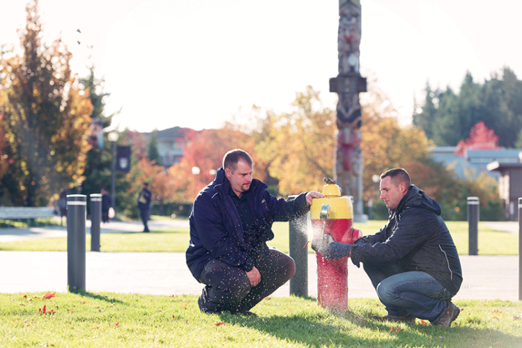 Roger Cerny and Paul McLaughlin testing at a campus hydrant by UBC's reconciliation pole. Image Credit: Martin Dee / University of British Columbia.